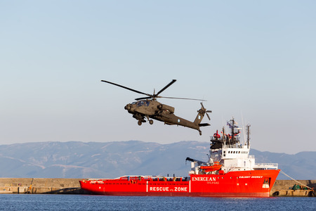 KAVALA, GREECE- JUNE 21, 2014: Apache AH-64 flying over energean ship during the Kavala Airshow 2014, in Kavala, Greece.