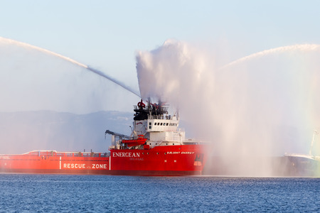 KAVALA, GREECE- JUNE 21, 2014: Valiant energy ship throws water during the opening ceremony for the exhibition for Kavala Airshow 2014, in Kavala, Greece. Editorial