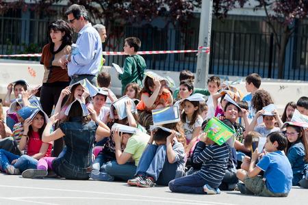 THESSALONIKI, Griechenland-24. April 2013: Kinder sitzen auf dem Schulhof, den Schutz ihrer Köpfe mit Bücher. Erdbebenübung, bohren. 6. Grundschule in Thessaloniki, Griechenland.
