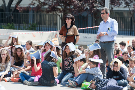 THESSALONIKI, GREECE- APRIL 24, 2013: Children sitting at the school yard, protecting their heads with books. Earthquake exercise, drill. 6th primary school in Thessaloniki, Greece.
