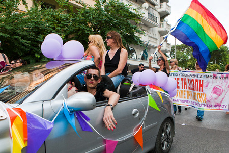 gay parade: THESSALONIKI, GREECE- JUNE 21, 2014: Participants with the rainbow flag in a car, the symbol of the gay rights movement, during the annual Gay Pride parade event in Thessaloniki, Greece. Editorial