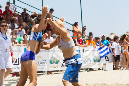 wrestle: KATERINI, GREECE- JULY 6, 2014: Two female athletes wrestle on sand during the First World Championship Beach Wrestling in 2014 in Katerini, Greece.  Editorial