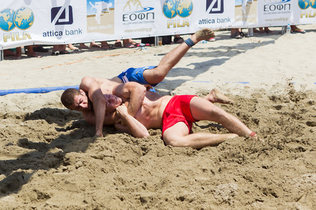 wrestle: KATERINI, GREECE- JULY 6, 2014: Two male athletes wrestle on sand during the First World Championship Beach Wrestling in 2014 in Katerini, Greece.