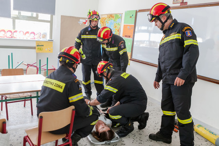 strapping: THESSALONIKI, GREECE- APRIL 24, 2013: Firemen strapping an injured woman to a stretcher during an earthquake exercise at 6th primary school in Thessaloniki, Greece.