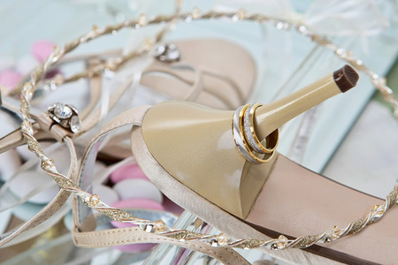 Wedding rings and high heel sandal. Composition.  photo