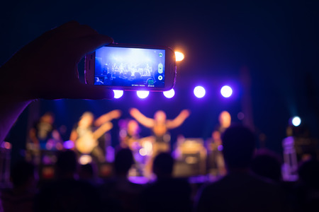 A fan watches a gig through his mobile phone. photo