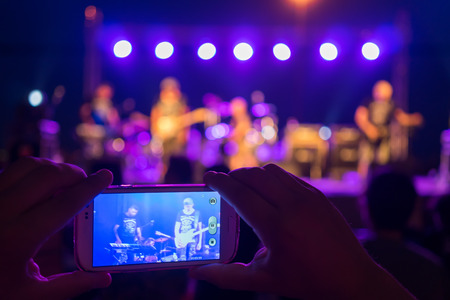 THESSALONIKI, GREECE- JUNE 27, 2014: Fan watches Band Blue Feathers performing live through his mobile phone in Thessaloniki, Greece.