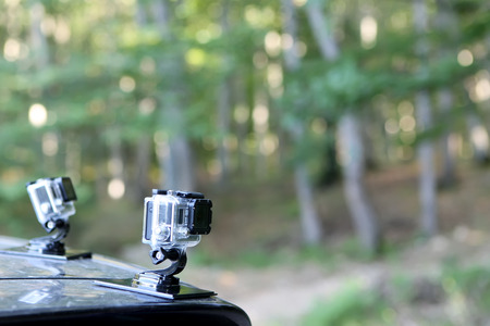 nyse: THESSALONIKI, GREECE  JULY 1, 2014: Gopro Hero 3 Cameras on the hood of a car in nature. Gopro went public June 26 2014 on the NYSE as symbol GPRO. Best selling action mini HD camera in the world.