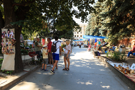 CHISINAU, MOLDOVA- AUGUST 21, 2014: Tourists and locals looking at the stalls at Chisinau flea market in Moldova. At the flea market one can find second hand clothes and shoes, souvenirs and paintings.