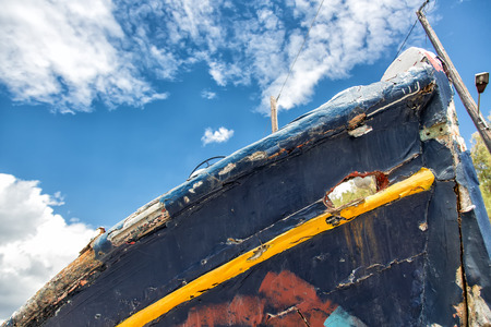 Detail of an old fishing boat rotting in the small harbor in Greece photo