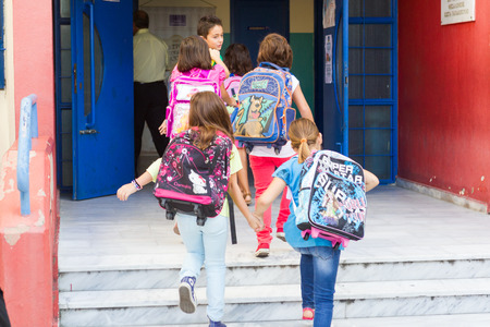 first day: THESSALONIKI, GREECE- SEPTEMBER 11, 2014: Students with their backpacks getting into school. First Day of school for the students in Thessaloniki, Greece.