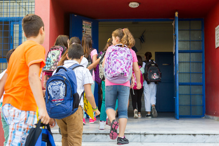 THESSALONIKI, GREECE- SEPTEMBER 11, 2014: Students with their backpacks getting into school. First Day of school for the students in Thessaloniki, Greece.