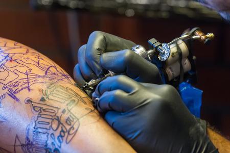 THESSALONIKI, GREECE- SEPTEMBER 19, 2014: Tattoo artist works in The 1st Thessalonink International Tattoo Convention, in Greece. Convention was held in Thessaloniki Port Warehouse C.