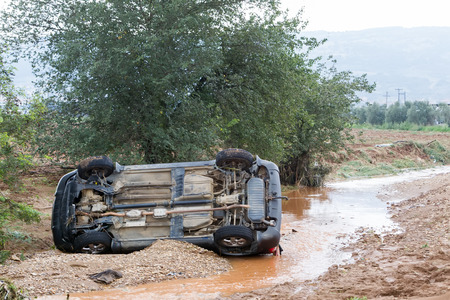 swerve: THESSALONIKI, GREECE- SEPTEMBER 15, 2014: Car overturned with one dead from the flood in Liti near Thessaloniki, Greece. Several main roads in Greece became flooded due to strong downpour.