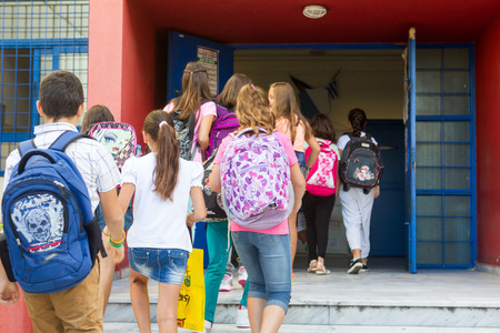 former years: THESSALONIKI, GREECE- SEPTEMBER 11, 2014: Students with their backpacks getting into school. First Day of school for the students in Thessaloniki, Greece.