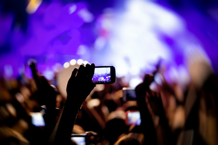famous industries: People taking photographs with touch smart phone during a music entertainment public concert Stock Photo