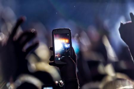 Las personas que toman fotografías con táctil de teléfono inteligente durante un concierto público de entretenimiento música
