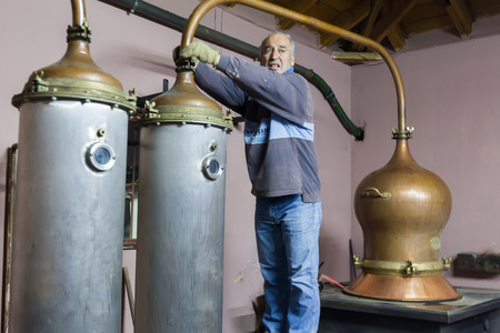 distillation: DRAMA, GREECE - NOVEBPER 15,2014: A man during the traditional distillation of alcohol and production of homemade tsipouroraki