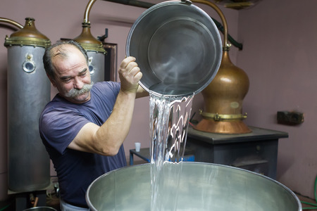 DRAMA, GREECE - NOVEBPER 15,2014: A man during the traditional distillation of alcohol and production of homemade tsipouro/raki