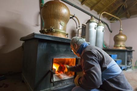 destilacion: DRAMA, GRECIA - NOVEBPER 15,2014: Un hombre durante la destilaci�n tradicional de alcohol y la producci�n de fabricaci�n casera tsipouro  raki Editorial