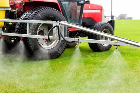 Tracteurs pulvérisés avec de l'engrais herbe sur le terrain