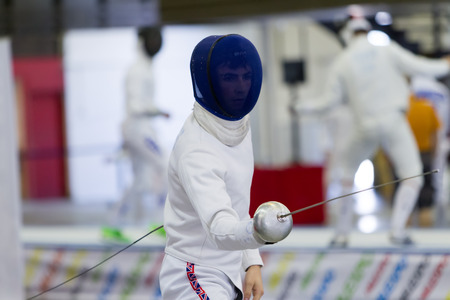 arbitrator: THESSALONIKI, GREECE - OCT 19, 2014 : Young athletes competing during the World Youth Fencing Championships 2014. Over 150 fencers from 25 countries took part at the championships.