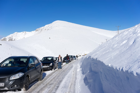 dramas: FALAKRO, GREECE - FEBRUARY 11, 2013: Visitors waiting near their cars for the Snowmobile to remove the snow from the road in Falakro, Greece. Falakro Mountain is located in the area of Dramas. Editorial