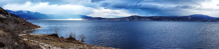 moody sky: Beautiful Landscape panoramic image of a mountain with moody sky and a lake in Greece.