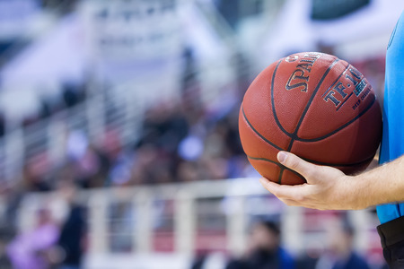 thessaloniki: THESSALONIKI, GREECE - JAN 21, 2015: Undefined referee hands holding a ball prior to Eurocup game Paok vs Khimki in Paok Sports Arena.