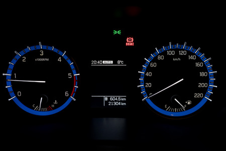 gauges: Backlit gauges of an automobile. Blue glowing meters with a white needle. Fuel, tachometer, and speedometer. Stock Photo