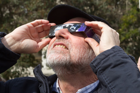 scheduled: THESSALONIKI, GREECE, MARCH 20, 2015: People use special glasses to look into the sky at a partial solar eclipse. Over Greece the moon was scheduled to cover approximately 45%. Editorial