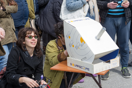 solar eclipse: THESSALONIKI, GREECE, MARCH 20, 2015: People watch through a telescope into the sky at a partial solar eclipse. Over Greece  the moon was scheduled to cover approximately 45% of the sun for a short period. Editorial