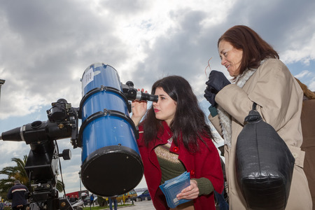 scheduled: THESSALONIKI, GREECE, MARCH 20, 2015: People watch through a telescope into the sky at a partial solar eclipse. Over Greece  the moon was scheduled to cover approximately 45% of the sun for a short period. Editorial