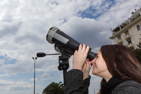 scheduled: THESSALONIKI, GREECE, MARCH 20, 2015: People use binoculars with special filters to look into the sky at a partial solar eclipse. Over Greece the moon was scheduled to cover approximately 45%.