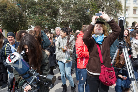 THESSALONIKI, GREECE, MARCH 20, 2015: People watch through a telescope into the sky at a partial solar eclipse. Over Greece  the moon was scheduled to cover approximately 45% of the sun for a short period. Editorial