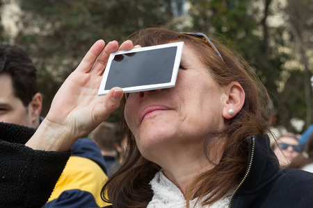 scheduled: THESSALONIKI, GREECE, MARCH 20, 2015: People use special filters to look into the sky at a partial solar eclipse. Over Greece the moon was scheduled to cover approximately 45%