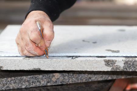 労働者は、切削大理石カッターを使用しています。