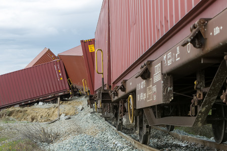derail: THESSALONIKI, GREECE, MARCH 28,2015: Derailed train coaches at the site of a train accident at the Gefyra community, in northern Greece. The train was carrying electronic equipment .