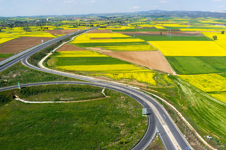 bioenergy: Aerial view of road passing through a rural landscape with blooming rape in northern Greece