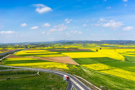 Aerial view of road passing through a rural landscape with blooming rape in northern Greece