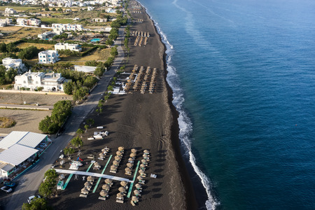 sharply: Top view of Perissa beach on the Greek island of Santorini with sunbeds and umbrellas. Beach is covered with fine black sand, and drops off sharply into the water.