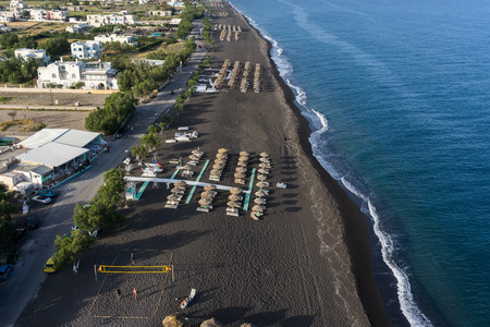 sharply: SANTORINI, GREECE - MAY 15,2015: Top view of Perissa beach on the Greek island of Santorini with sunbeds and umbrellas. Beach is covered with fine black sand, and drops off sharply into the water.