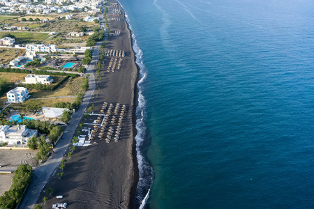 sharply: SANTORINI GREECE  MAY 152015: Top view of Perissa beach on the Greek island of Santorini with sunbeds and umbrellas. Beach is covered with fine black sand and drops off sharply into the water.