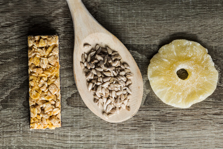 energy bar: Seeds in Wooden Spoon Spread on Wood Background with energy bar and dried pineapple. Stock Photo
