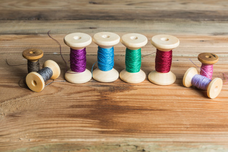 old spools: Spools of thread on wooden  background. Old sewing accessories. colored threads Stock Photo