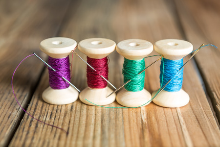 old spools: Spools of thread with needles on wooden background. Old sewing accessories. colored threads Stock Photo