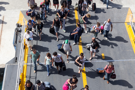 too many: PAROS, GREECE, MAY 17, 2015: Passengers board the ship at the port of Paros in Greece.The Paros is an island in Cyclades that accepts too many tourists every year Editorial