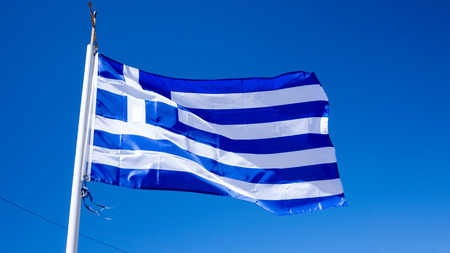 greek currency: national flag of Greece against blue sky background