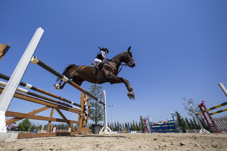 THESSALONIKI, GREECE, JUNE 14, 2015: Unknown rider on a horse during competition matches riding round obstacles Redakční
