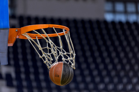 prior: THESSALONIKI, GREECE, JUN 17, 2015: Basketball ball going through the net prior to the Greek Basket League game Aris vs Paok Editorial